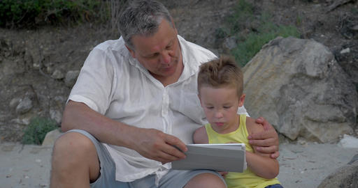 Grandson and grandfather with touch pad outdoor Footage