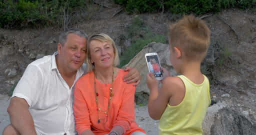Child taking picture of grandparents with cell phone Footage