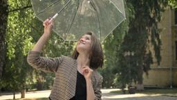 Young attractive girl opens and spins umbrella in park in daytime, in summer Photo