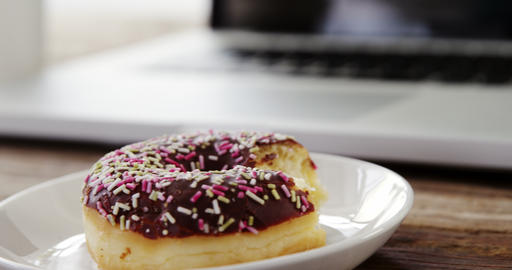 Half eaten chocolate doughnut with sprinkles on wooden table Footage