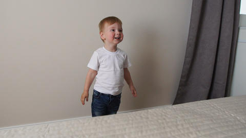 The boy is standing in front of the parents' bed and having fun with their Footage