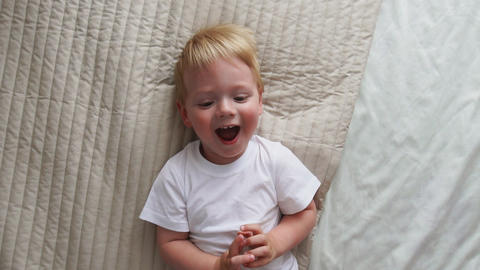 Mom tickles the boy lying on the bed who looks directly into the camera and Footage