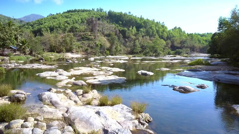 big stones in river against tropical trees and mountains Footage