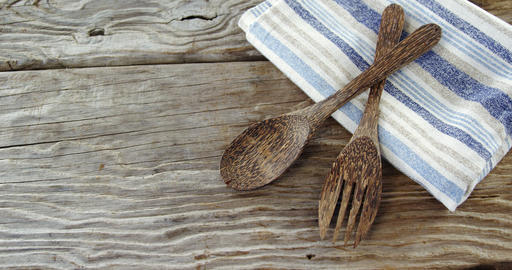 Wooden spoon and fork with napkin on table Live Action