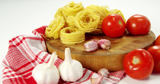 Tomatoes and raw pasta on chopping board Footage