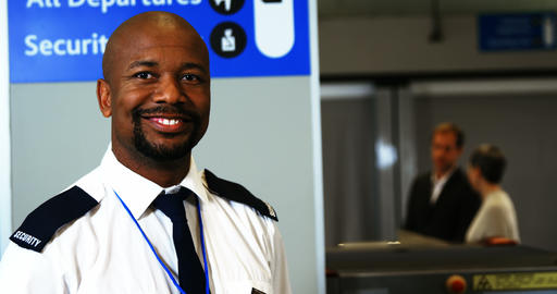 Smiling security staff holding metal detector standing at airport Live Action