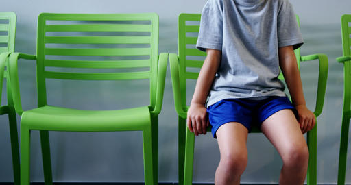 Upset boy sitting on chair in hospital corridor Footage