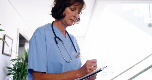 Nurse writing a report on clipboard Footage