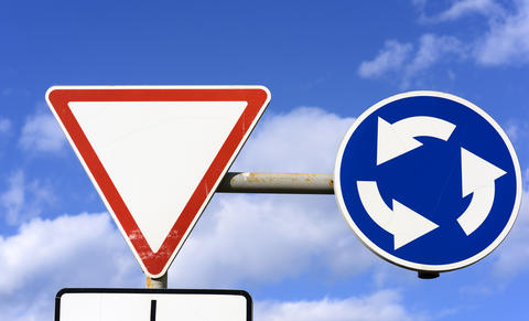 two road signs against a blue sky with white clouds フォト