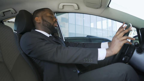 African-American man in suit sitting in car and yawning, driver of businessman ビデオ