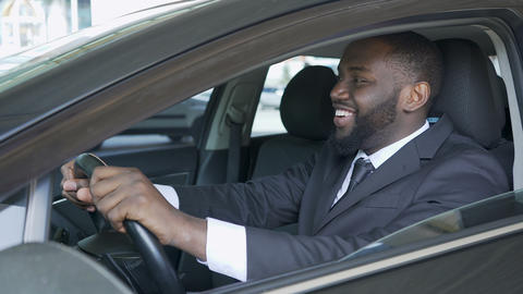 African American man sitting in expensive car satisfied and smiling, test drive Live Action