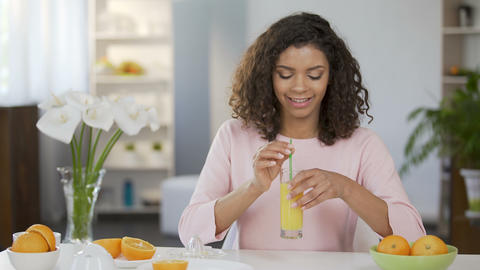 Young multiracial female drinking juice from glass, healthy juicing, vitamins Footage
