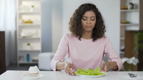 Attractive woman sadly choosing salad over cake, diet, weight control, nutrition Footage