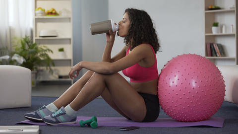 Sporty woman sitting on floor in gym outfit and drinking supplement cocktail Live Action