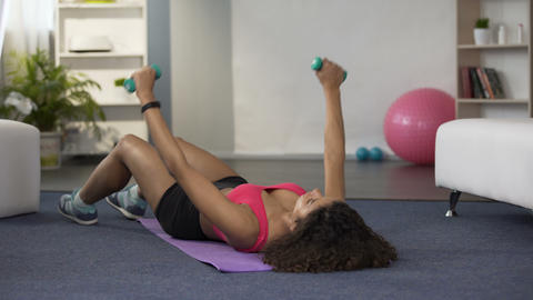 Young woman lying on floor and lifting dumbbells, physical exercises, fitness Footage