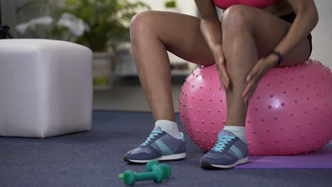 Sporty young woman warming up legs before working out, physical activity start Footage