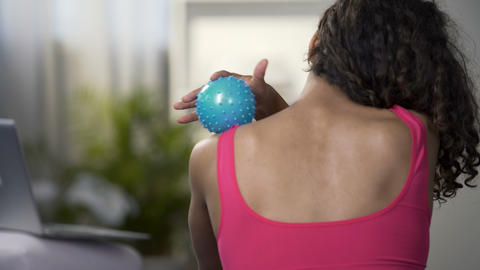 Young woman massaging shoulders with ball, soothing muscles after working out Footage