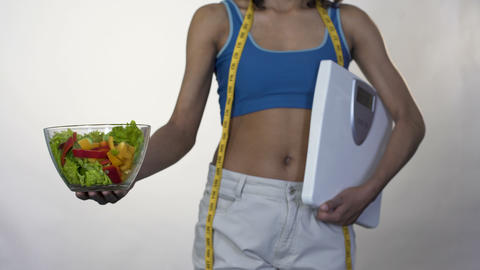 Woman in loose pants standing with scales, holding out bowl of salad, dieting Footage
