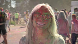 Young pretty blonde girl with sunglasses is thrown with colorful powder on holi Footage