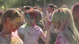 Three young happy multi-ethnic girlfriends are dancing and smiling on holi Footage
