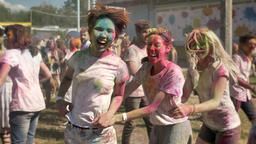Three young happy multi-ethnic girlfriends are doing conga line on holi festival Footage