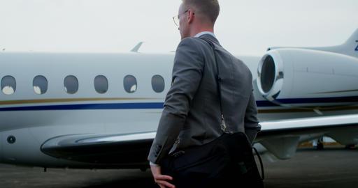 Businessman walking towards private jet 4k Footage