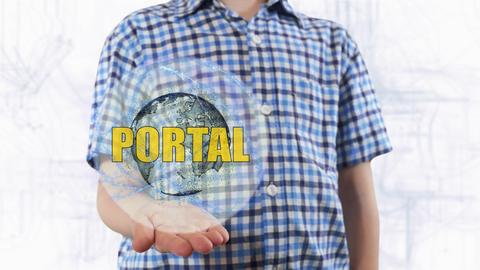 Young man shows a hologram of the planet Earth and text Portal Photo