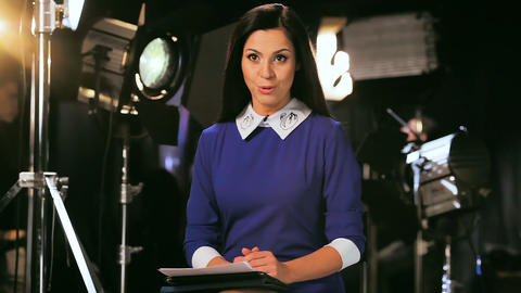 TV-presenter in blue blouse talks to audience at set ビデオ