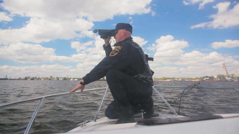 officer sits and looks through binoculars on launch Footage