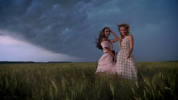Two young charming girls in dresses is enjoing wind in field in rainy day in Footage