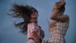 Two young charming girls in dresses is enjoing wind, touching hair in field in Footage