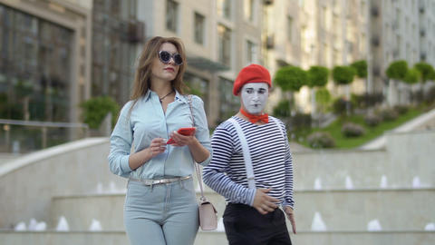 Mime has fun near the stylish woman using phone Footage