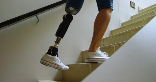 Disabled woman with prosthetic leg moving upstairs 4k Footage