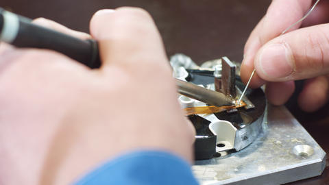 worker repairs device part using heated melting tool Footage