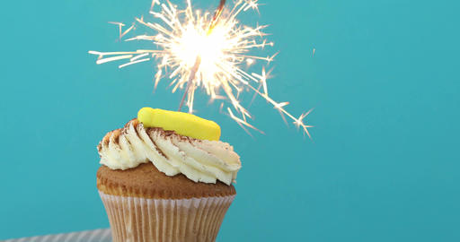 Cupcake with sprinkles and sparkler blue background Footage
