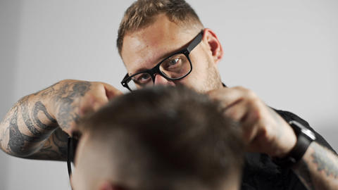 Tattoed barber makes haircut for customer at the barber shop by using scissors Footage