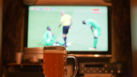 Television, TV watching (football, soccer match) with beer on table Archivo