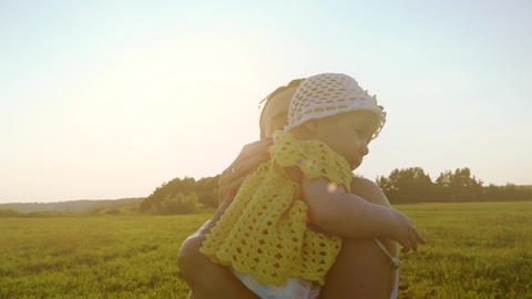 Slow motion shot of happy mother hugging her little baby girl at sunset Footage