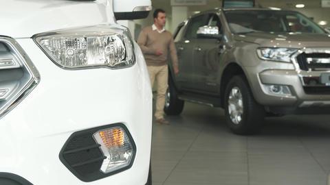 A solid man walks among cars at the car dealership ビデオ