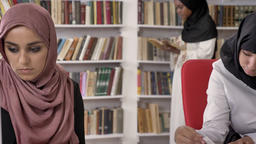 Three young muslim womens in hijab studying in library, reading and writing Footage