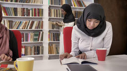 Three young muslim womens in hijab reading books in library, studying for exam Footage