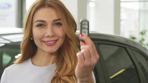 Cheerful attractive woman smiling showing car keys to the camera at the Live Action