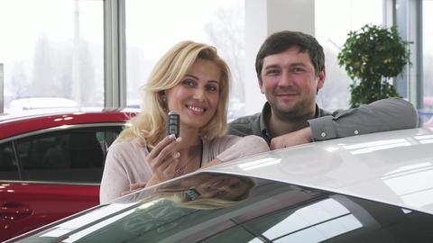 Beautiful happy mature couple posing near their new auto holding car keys Footage