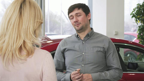 Happy mature man handing car keys to a new auto to his loving wife Footage