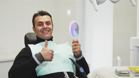 Happy mature man showing thumbs up after dental examination Live Action