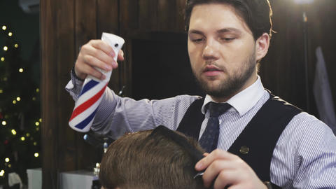 Professional barber spraying hair of his client while styling Footage