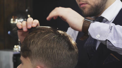 Close up of a professional barber spraying hair of a client with water Footage