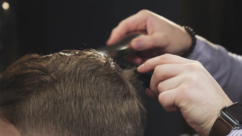 Cropped close up of a barber cutting hair of his client with a trimmer Footage