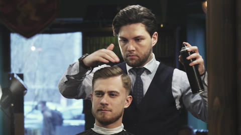 Professional barber using hairspray styling hair of a young man Footage