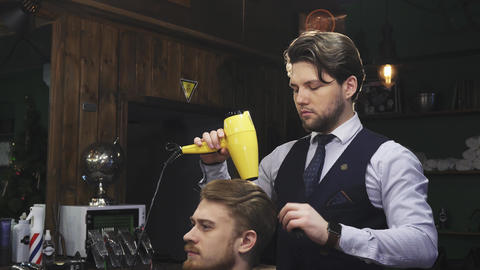 Handsome bearded professional barber working with his client Footage